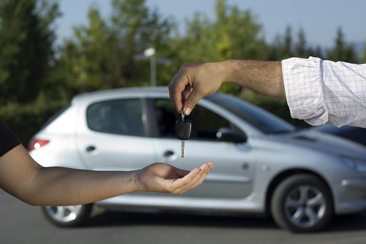 Person receiving key after they buy a used car